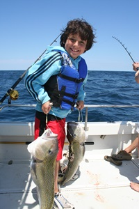 Your kids will be miserable if you force them to wear bulky, uncomfortable lifejackets. While young David Rudow is happy about his double tilefish hookup here, also note the easy-to-wear lifejacket his dad has fitted him with. Photo by Lenny Rudow.
